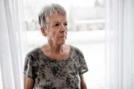 Sad senior woman at home close to window