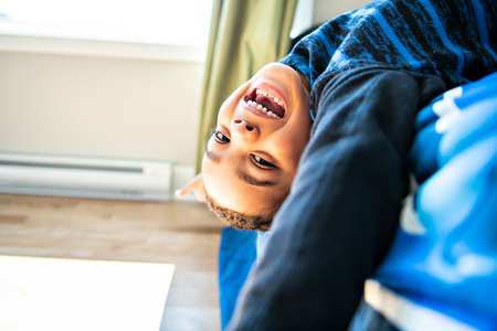 A Cute portrait of child upside down, lying on bed, smiling at camera and playing with toy
