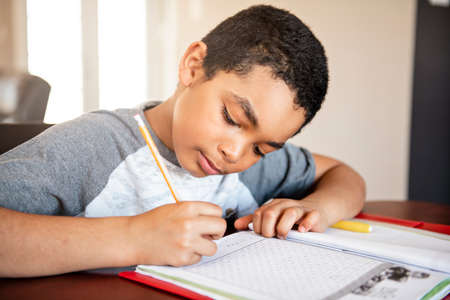 A male black child doing homework at home Standard-Bild