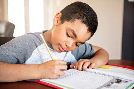 A male black child doing homework at home Banco de Imagens