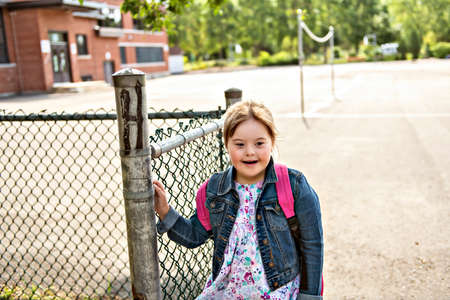A portrait of trisomie 21 child girl outside on a school playground Stockfoto