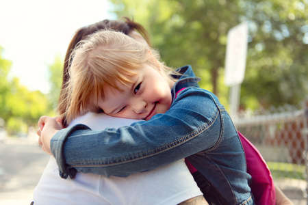 A portrait of trisomie 21 child girl outside hugging his mother on a school playground