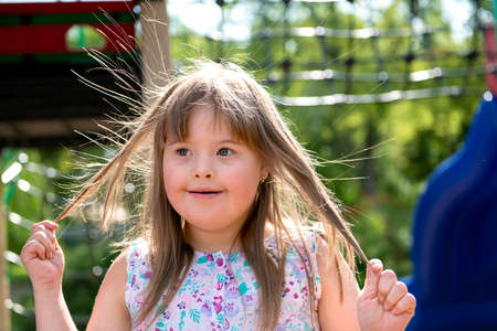 A portrait of trisomie 21 child girl outside having fun on a park Stock Photo