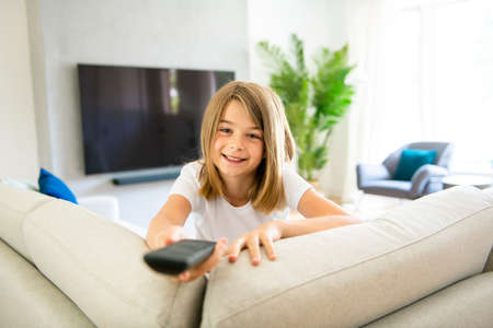 A girl holding remote control and watching TV show