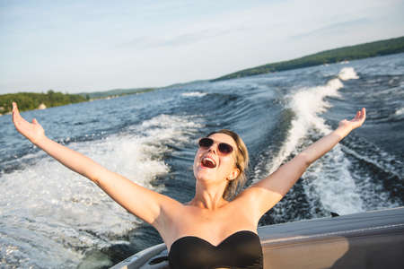 A beautiful sexy happy girl ride on a speed boat