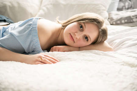 A teenage girl lying in bed and relaxing Stock fotó