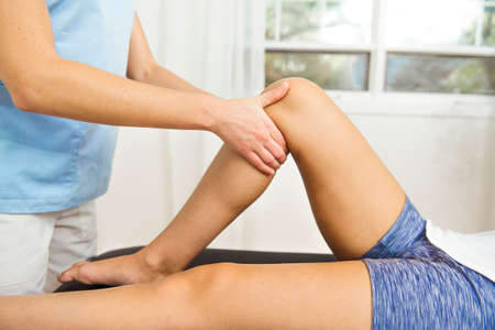 A Modern rehabilitation physiotherapist at work with client. working on knee
