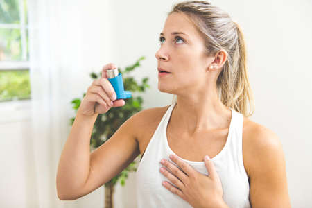 A Young woman using asthma inhaler at home