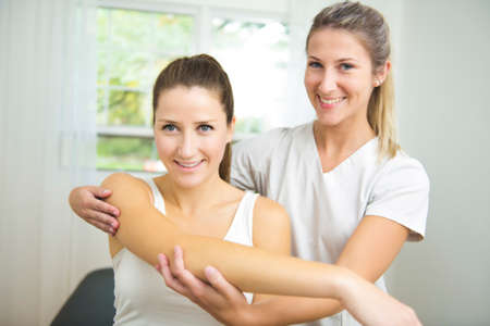 A Modern rehabilitation physiotherapist at work with client. working on shoulder. Stock Photo