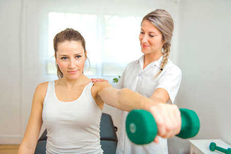 A Modern rehabilitation physiotherapist at work with client. Working on shoulder with dumbell Standard-Bild