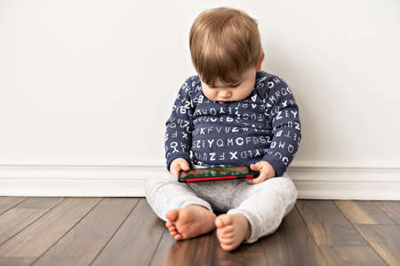 A little boy toddler sitting and watching plays in the tablet cellphone Banco de Imagens
