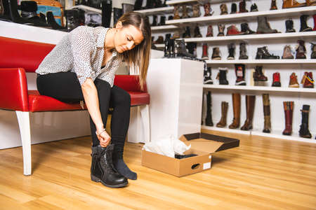 A Beautiful young woman trying boot while sitting at the shoe store