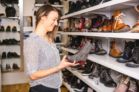 A woman looking for the best boot in a shop Standard-Bild