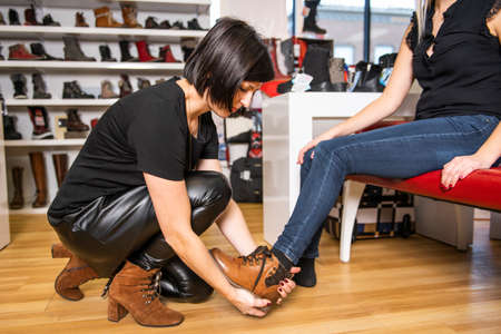 A seller propose to try shoes to a female client