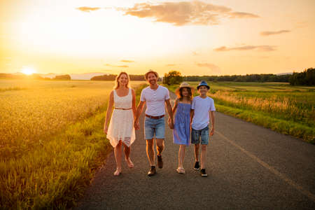 happy family at sunset. They having fun and playing in nature at sunset