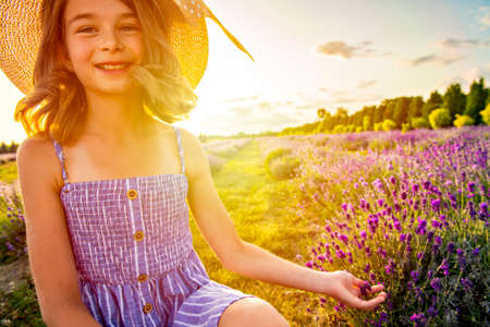 portrait of young blonde girl in the colour dress in the field of lavander