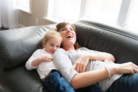 Happy mother with her daughter on the sofa in the living room at home