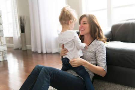 Happy mother with her baby daughter in the living room at home Stock fotó