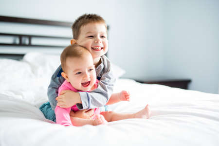 A baby and his brother on bed having fun