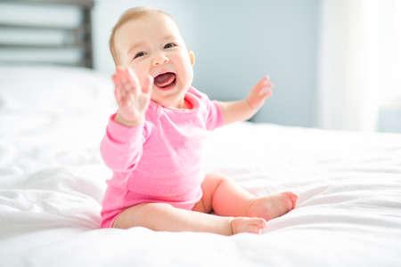 baby girl sit on white sheet