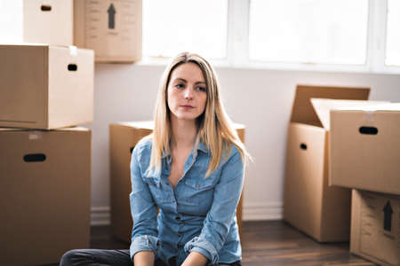 A sad woman with box at home