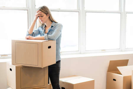 A depress woman with box at home