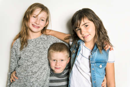 Childhood, love, happiness and family bonds. Indoor portrait of beautiful cute children sisters and brother Reklamní fotografie