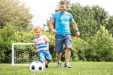 Man with child playing football outside on field Archivio Fotografico