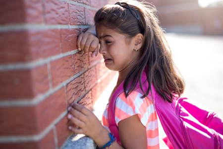 six years old school girl cry beside brick wall