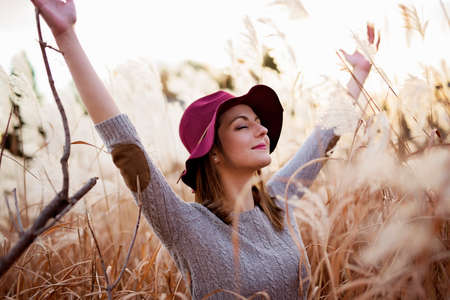 Woman in a wheat field at sunset