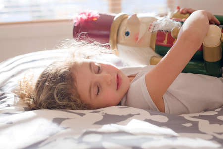 Beauty child who holding a nutcracker in bed Stock Photo
