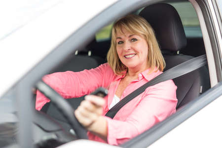 Happy and smiling senior woman in black car Stock Photo
