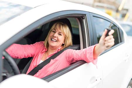 Happy and smiling senior woman in black car Standard-Bild