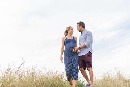 pregnant woman at beach with husband having fun
