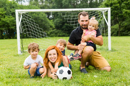 Happy family with football ball on a field