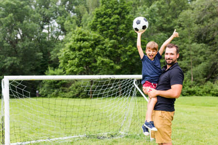 father with son playing football on football pitch