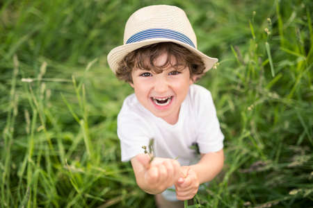 Portrait of adorable kid boy with hat standing on a summer meadow Banco de Imagens