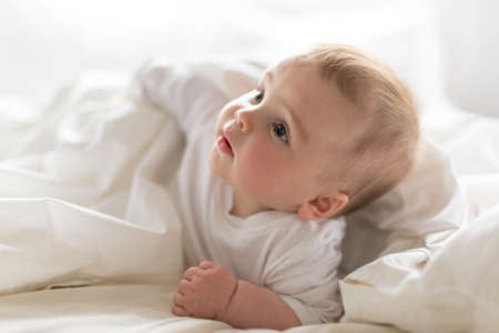 Cute happy 7 month baby girl in diaper lying and playing Archivio Fotografico