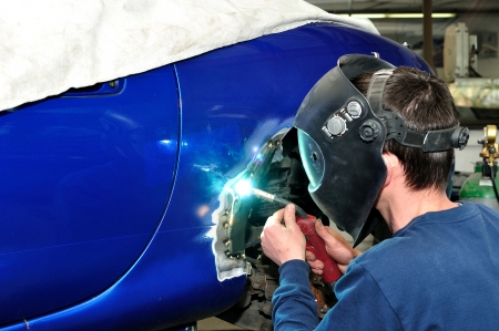 auto garage: worker welding car body