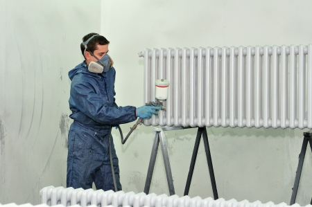Worker painting a heater
