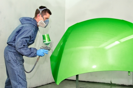 Worker painting a car bonnet