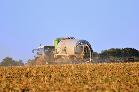 manure: Tractor with sprayer working on field  Stock Photo