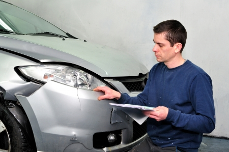 Insurance expert examining car damage