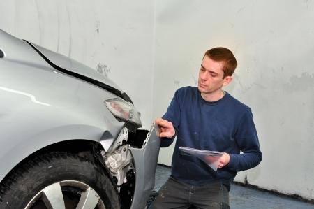 Insurance expert examining car damage  photo