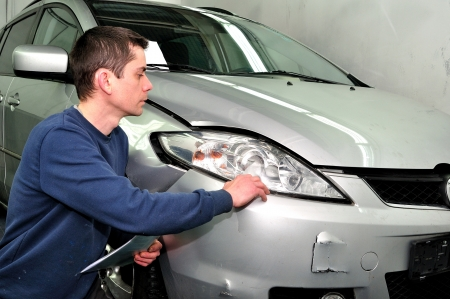 bumps: Insurance expert examining car damage