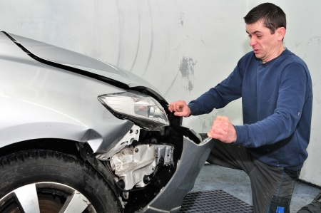 Angry worker repairing a car in a different way  photo