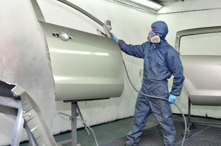 Worker painting silver car door  Stock Photo - 18401634