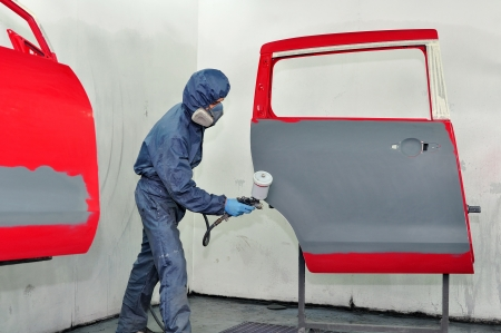 Worker painting red car door