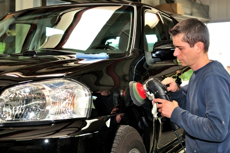 Body shop worker polishing black car