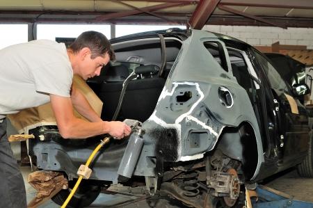 body work: Car mechanic at work in body shop  Stock Photo